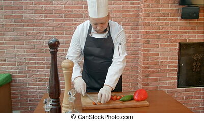 Chef cutting tomatoes in the kitchen. Professional shot in...