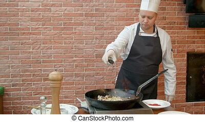 Chef putting spoons with spices to the pan, prepearing...