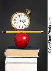 Education - Clock and pencil balancing on top of a pile of...