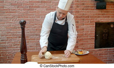 Chef kneading a dough. Professional shot in 4K resolution....