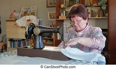 Adult woman sews on the old manual sewing machine. Glasses...