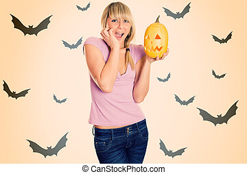 Halloween - A young girl terrified screams with a pumpkin...