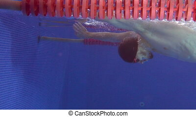 The professional swimmer making a turn underwater and pushing off the wall with feet.