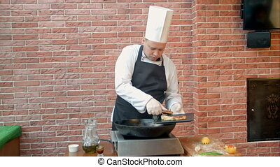 Chef putting fried dumplings with seafood on plate....