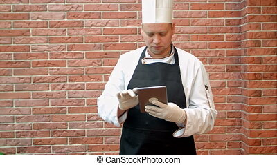 Chef using his digital tablet in the kitchen. Professional...