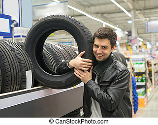 male customer choosing new tires - Glad male customer buying...