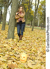 Halloween - Young girl outdoors in autumn in the park with a...
