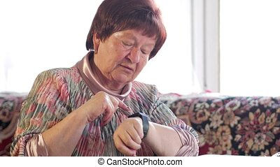 An elderly woman checks the messages on a smart watch. She...
