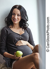 Cute happy pregnant woman on window sill with apples in the room, close up