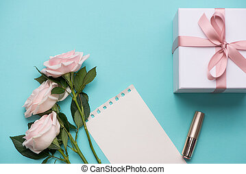 Mother's Day concept. Bouquet of pink roses with gift box and lipstick. Blank paper note for copy space.