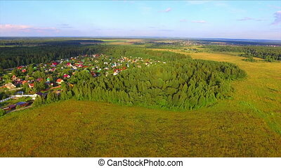 Aerial view of countryside and village on background
