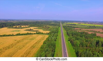 Drone flight over the highway among the ripe rye fields and...