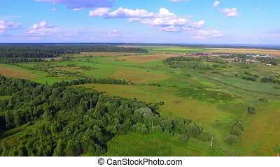 Aerial view of fields, forests and a village on background