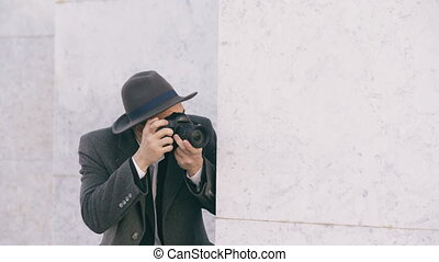 Young paparazzi man in hat photographing celebrities on camera while spy behind the wall
