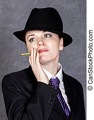 Young woman in manly style with mini cigar on gray...