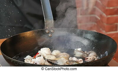 Cooking seafood in a pan with olive oil and parsley. Close...