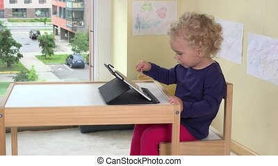 Happy blond girl touching tablet computer screen with finger...