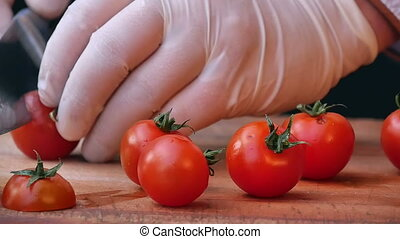 Cutting tomatoes for dishes on the table. Close up. Slow...