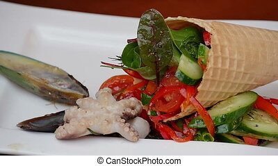 Putting seafood to a vegetable salad on a plate. Close up....