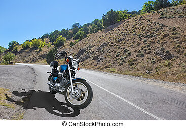 Motorbike on a country road near a mountain