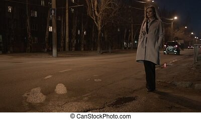 A young woman was lost in a night city. The beautiful blond tourist has lost her way and does not know where to go. A woman is standing by the road, cars are rushing past.