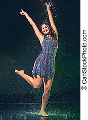 Young beautiful woman under splash of rain