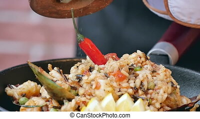 Putting saly to paella, finishing the dish. Close up. Slow...