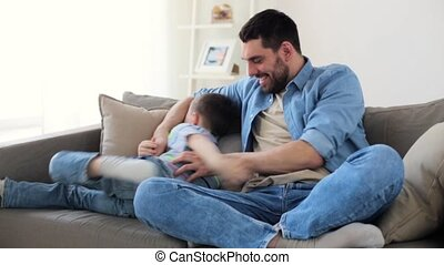 father with son playing and having fun at home - family,...