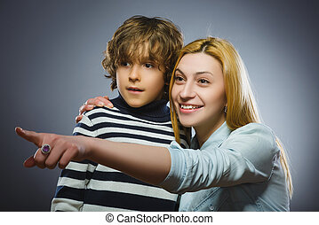 Mother holding boy and showing something away isolated on...