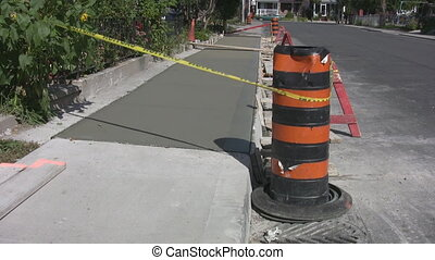 Sidewalk with wet cement. - New cement section in the...