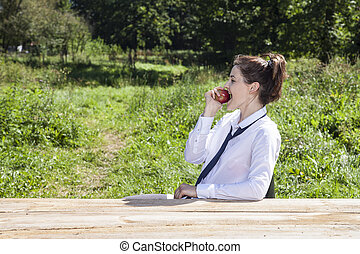 young business woman eating an apple during break