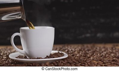 Pouring coffee in white cup surrounded by coffee beans on dark background. 4k
