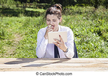 business woman eating an apple and reading messages