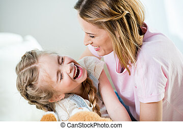 Happy mother and daughter having fun together at home