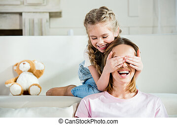Happy mother and daughter having fun and playing at home