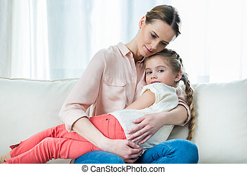 portrait of pensive mother holding daughter while sitting on sofa