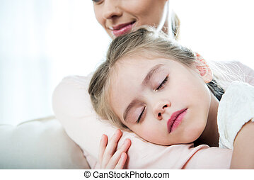 little girl sleeping on mother's arm at home