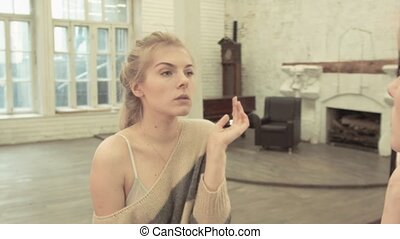 Sexy blonde powder spout near the big mirror. A happy young woman is getting ready to meet her beloved.