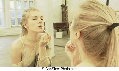 Sexy blonde paints lips at the mirror and smiles. A...