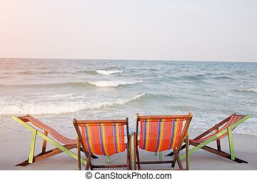 Two deck chairs on beach during day