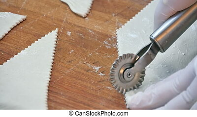 Cutting dough with roller knife on table. Close up. Slow...