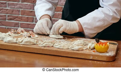 Making dumplings with seafood on wooden board. close up....