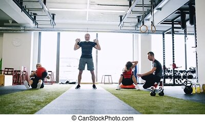 Fit seniors in gym with personal trainer doing various...