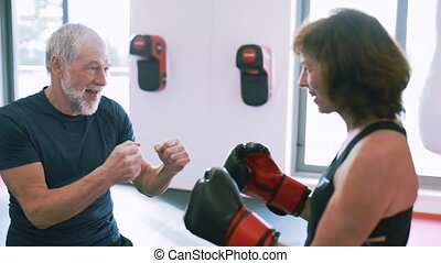 Fit senior couple in gym explaining boxing. - Beautiful fit...