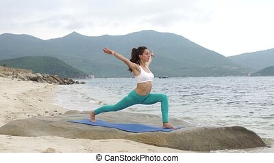 Young healthy sporty woman practicing yoga on the beach at sunset.