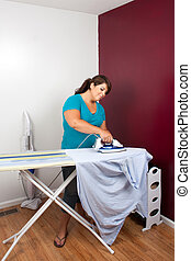Woman Ironing Clothes - A young woman at home pressing some...