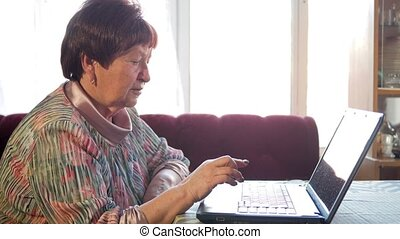 An older woman checks the messages on social networks on a laptop at home. She sits at the table