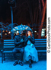 Guy and girl sitting on a bench under an umbrella on a night...