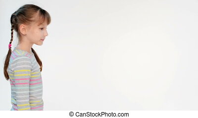 Calm little girl standing with folded hands looking at...
