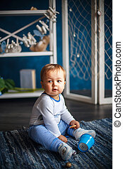 Portrait of a cute little baby in the interior with sea style